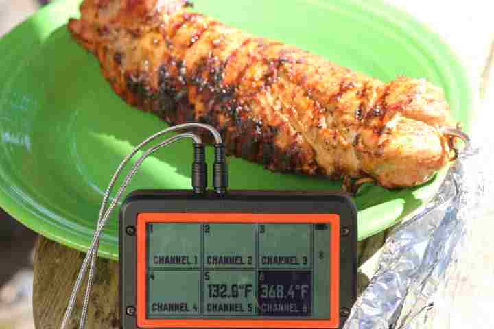 A pork tenderloin just pulled off the grill registering 132.9 degrees Fahrenheit on a meat thermometer
