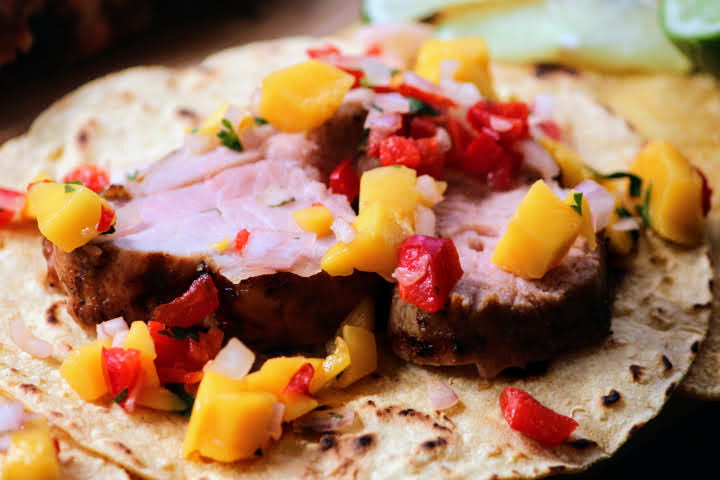 Two pieces of grilled pork tenderloin sliced thin on a corn tortilla topped with mango salsa