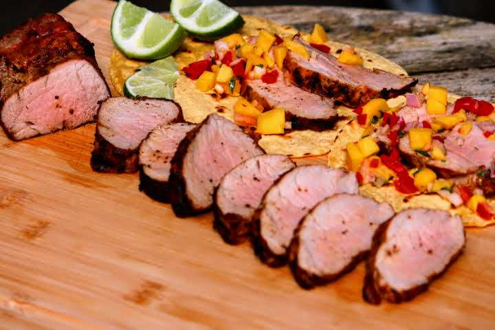 Mesquite charcoal grilled pork tenderloin sliced into pieces on a cutting board along with two pork tenderloin tacos with mango salsa