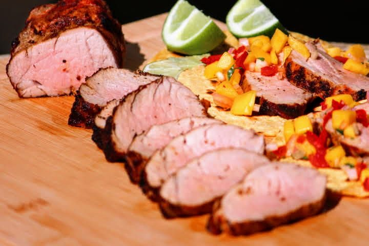 Grilled pork tenderloin slice on a cutting board