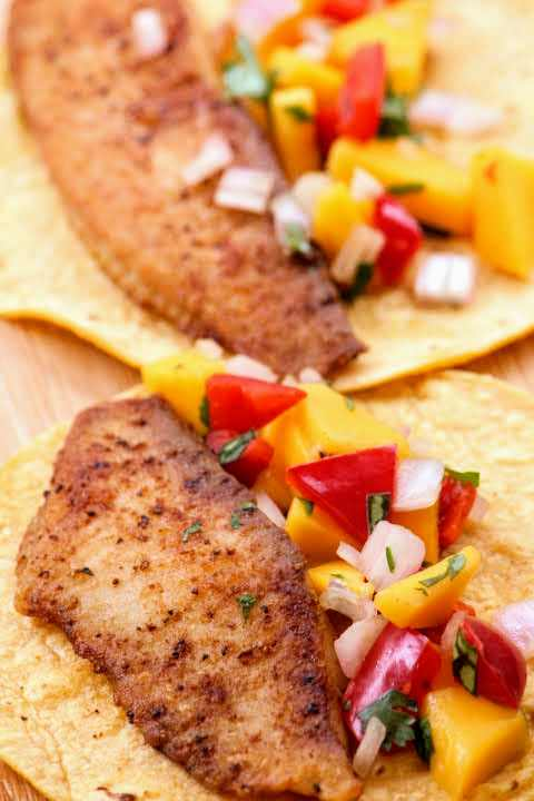 Two spice-rubbed tilapia fillets in corn tortillas topped with mango salsa