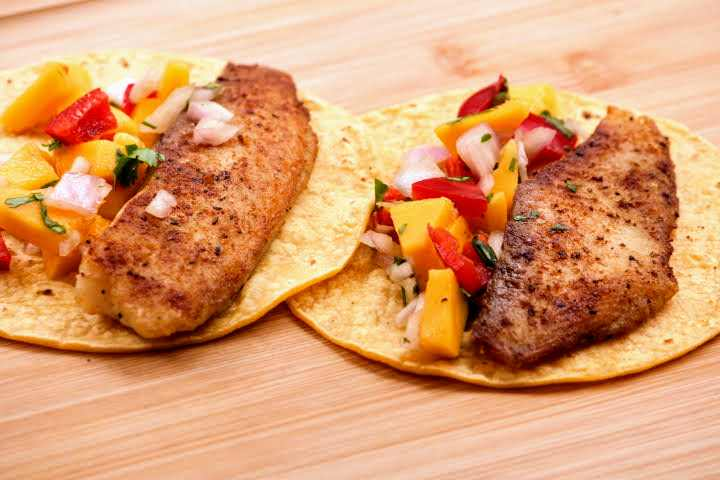 Two tilapia tacos topped with mango salsa side by side on a cutting board