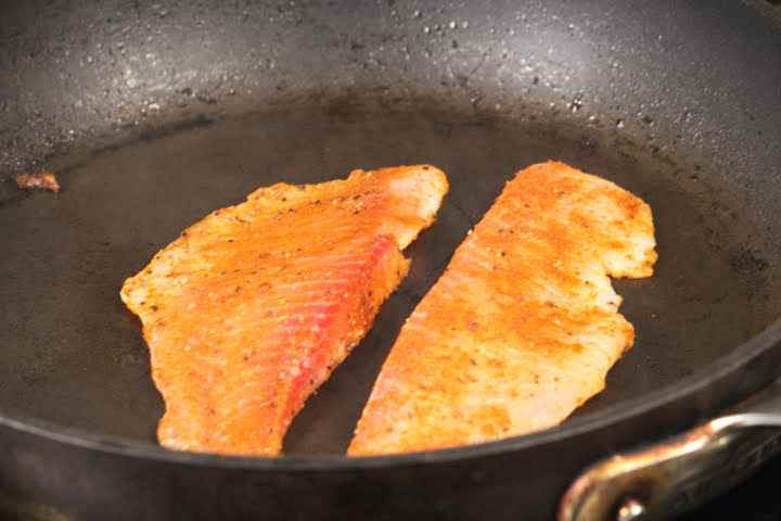 The thinner top portions of tilapia fillets cooking in a pan over medium heat on the first side