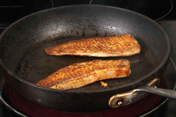 Tilapia belly pieces flipped over in a pan over medium high heat
