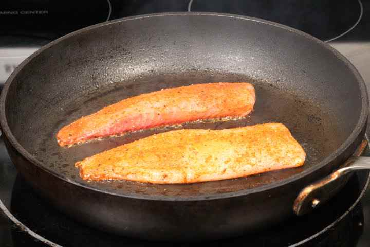 Two tilapia belly pieces cooking in a skillet over medium-high heat