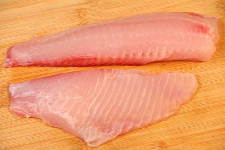 A raw tilapia fillet cut in half along its backbone into two smaller pieces