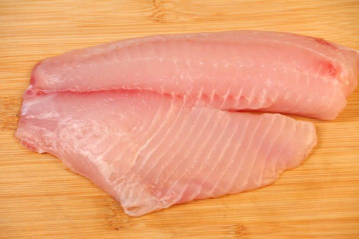 A raw tilapia fillet on a cutting board