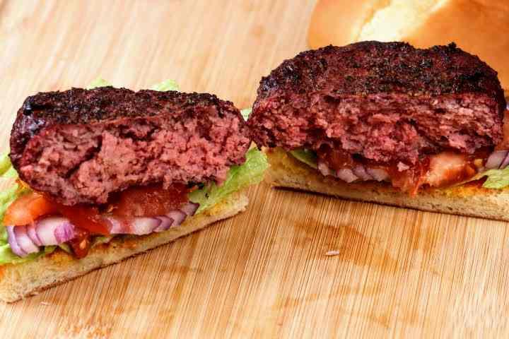 A smoked hamburger on a bun cut in half revealing its interior with a visible smoke ring.