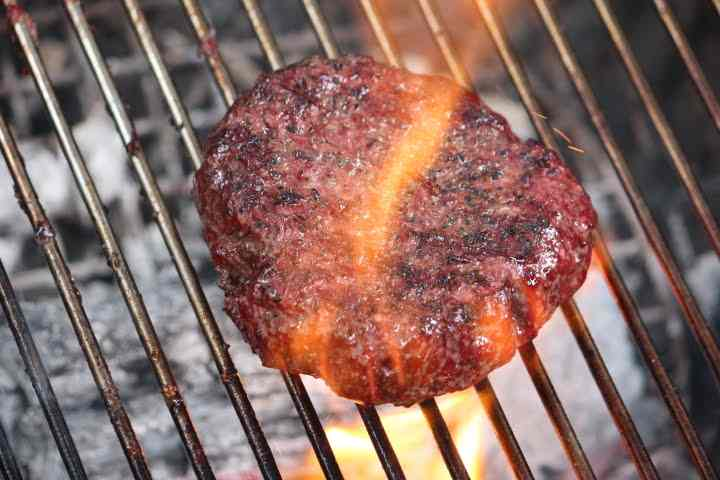 Finishing a smoked hamburger on a grill grate directly over hot coals