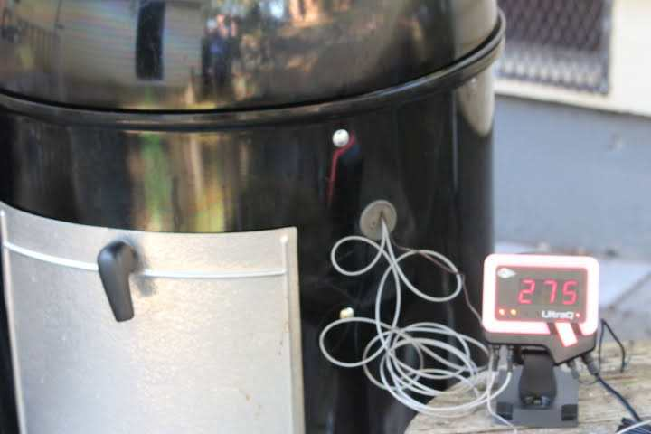 The BBQ Guru Ultra Q registering a temperature of 275 degrees Fahrenheit on its display while monitoring food in a Weber Smokey Mountain Grill