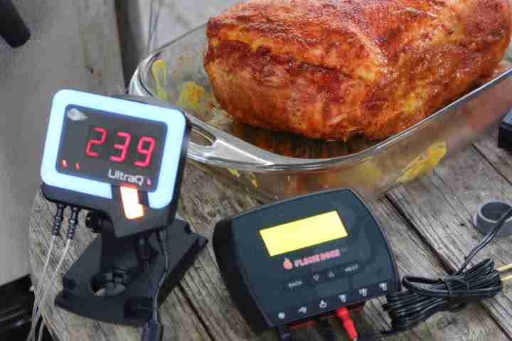 The BBQ Guru UltraQ displaying a temperature of 239 degrees Fahrenheit with a blue Guru status light ring indicating it's below your set pit temperature