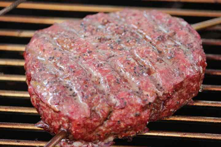 A smoked hamburger with a visibly reddish exterior due to the smoke it's absorbed