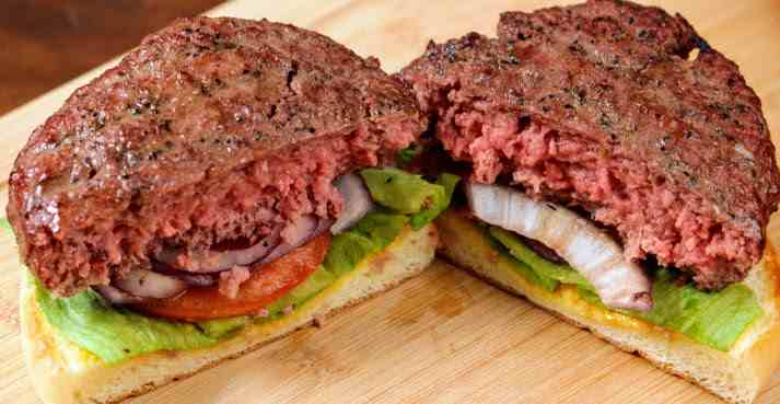 A hamburger that's been smoked and seared to an internal serving temperature of 147 degrees Fahrenheit and cut in half to reveal a pink medium-rare middle