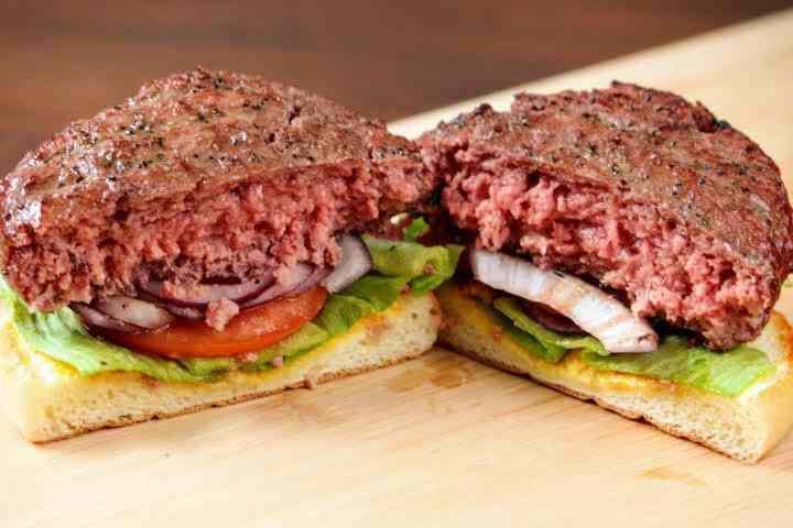 A smoked hamburger cut in half revealing a medium-rare interior