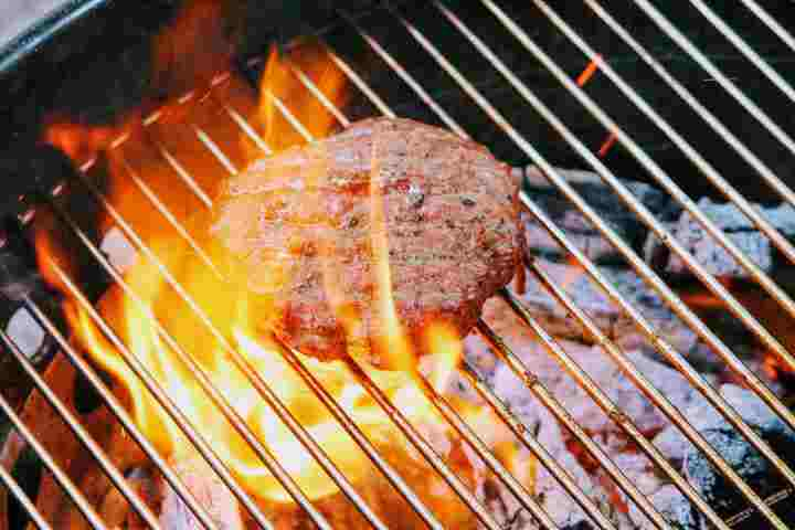 Grilling a hamburger directly over hot coals with flames shooting up throught the grates due to the fat hitting the coals