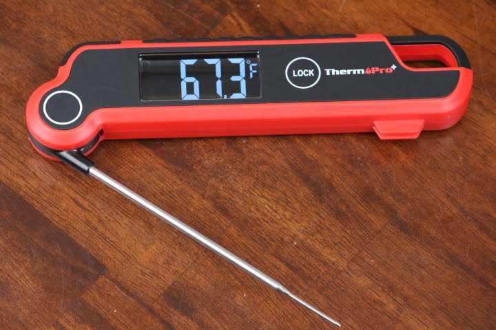 ThermoPro TP620 Digital Instant-REad Meat Thermometer lying on a table displaying a temperature of 67.3 degrees Fahrenheit