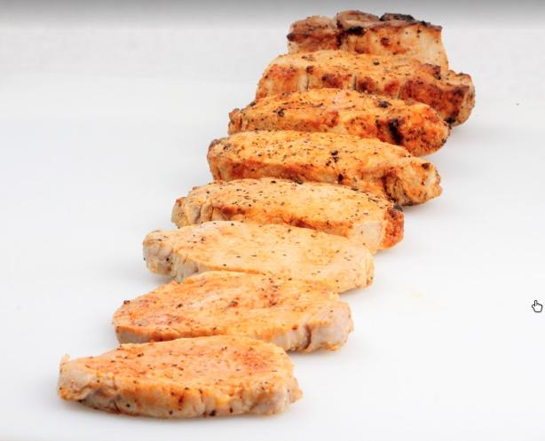 Eight boneless pork chops on a cutting board arranged in thcikness going from 1/4 thick to 2 inches thick