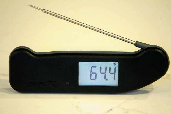 A black Thermapen ONE thermometer registering 64.4 degrees Fahrenheit while upside down on a white countertop