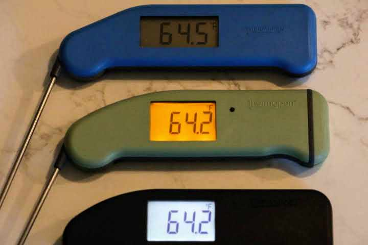(From the top), A Classic Blue Thermapen, a Pistachio-colored Thermapen MK4, and a Black Thermapen ONE meat thermometer displaying their backlit screen abilities