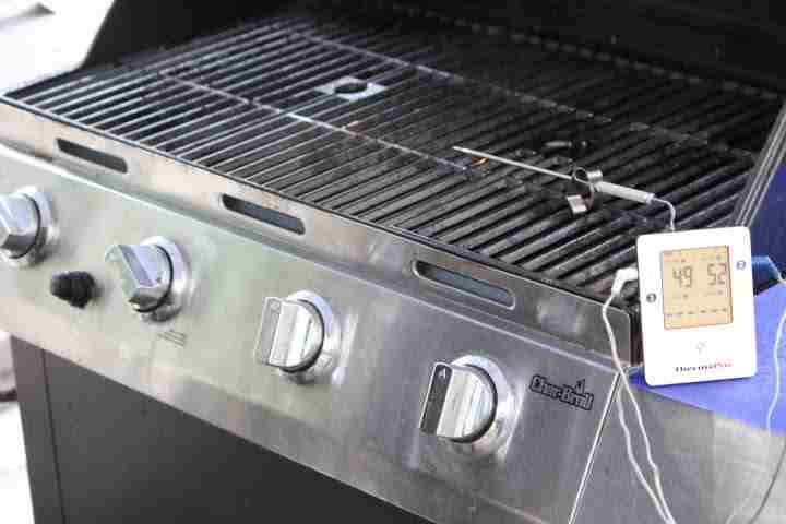 Setting up a gas grill for indirect smoking with a wireless thermometer tracking the grill's temperature