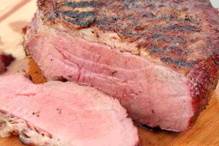 Smoked tri tip sliced with its fat cap left on and still clearly prominent after smoking