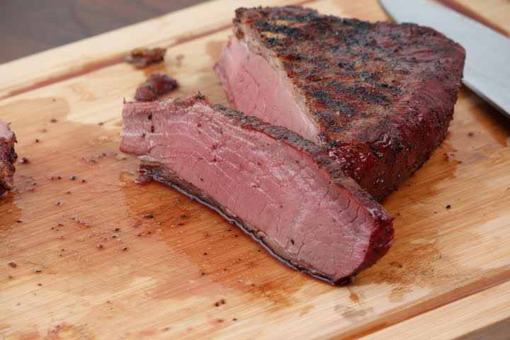 Smoked Tri Tip on a cutting board with a slice revealing a medium-rare doneness with a thin pink smoke ring