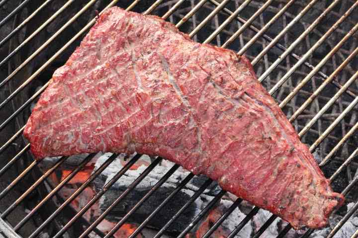 Smoked Tri Tip being seared on a charcoal grill to finish