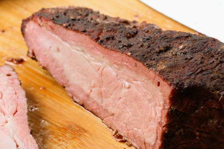 A smoked tri tip cut open to reveal a thick smoke ring around the outer portion of the meat