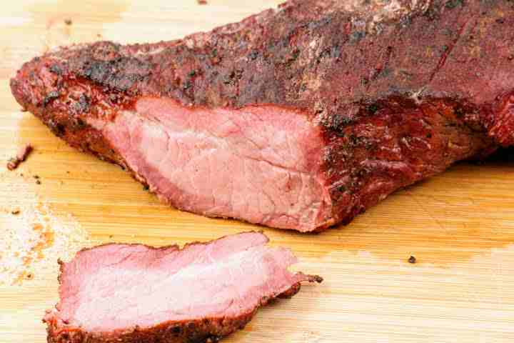 A smoked tri tip with a corner cut off revealing meat with a very thick smoke ring